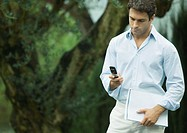 Man using cell phone outdoors, holding documents