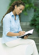 Woman writing outdoors
