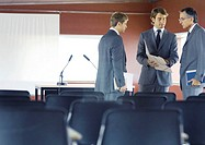 Executives standing, speaking in conference room