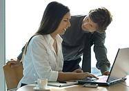 Female office worker using computer, businessman leaning over her shoulder