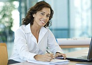 Businesswoman sitting at desk, smiling at camera