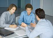 Three young business men working at table