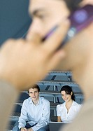 Young business professionals, man using cell phone in blurred foreground