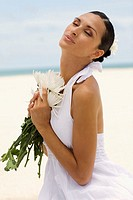 Side profile of a young woman holding flowers on the beach