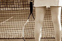 Mid section view of a woman holding a tennis racket