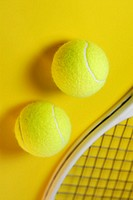Close-up of two tennis balls with a tennis racket