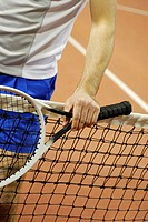 Mid section view of a man holding a tennis racket