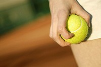 Close-up of a person's hand holding a tennis ball