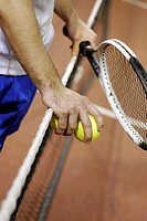 Mid section view of a man holding two tennis balls and a tennis racket