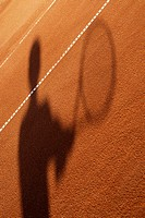 Shadow of a person holding a tennis racket