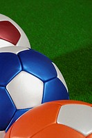 Close-up of three soccer balls on the grass