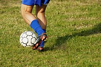 Low section view of a soccer player dodging a soccer ball