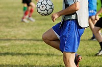 Mid section view of a soccer player balancing a soccer ball on his thighs