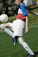 Side profile of a soccer player balancing a soccer ball on his thighs