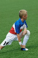 Soccer player stretching in a soccer field