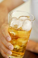 Close-up of a human hand holding a glass of whiskey