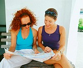 Close-up of two young women sitting on a bench and reading a newspaper, Bermuda (thumbnail)