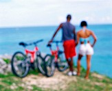 Rear view of a young couple standing with bicycles on the coast, Bermuda