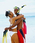 Side profile of a young couple embracing each other and holding flippers, Bermuda