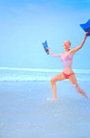 Woman holding flippers and running in surf at beach
