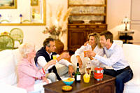 Senior couple and young couple toasting in livingroom