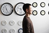 Side profile of a businessman standing in front of clocks on the wall