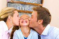 Parents kissing daughter´s cheeks indoors