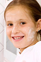 Young girl smiling with flour on cheek