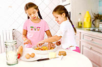 Two young sisters preparing food in kitchen