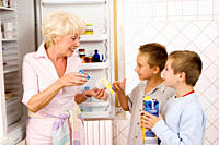 Grandmother giving grandsons food from refrigerator