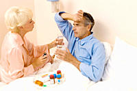 Senior man in bed getting medication from senior woman