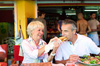 Senior couple eating at outdoor restaurant