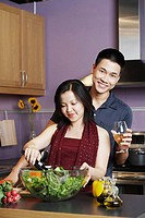 Young man standing holding a wineglass with a young woman preparing food