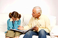 Grandfather and granddaughter with binder on sofa
