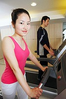 Side profile of a young woman and a young man exercising in a gym