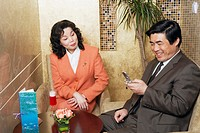 Businessman sitting with a businesswoman in a restaurant looking at a mobile phone