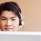 Close-up of a male customer service representative talking on a headset and using a laptop