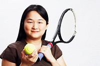 Portrait of a mid adult woman holding a tennis ball and a tennis racket
