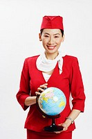 Portrait of an air stewardess holding a globe and smiling