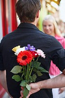Rear view of a man hiding a bunch of flowers behind his back