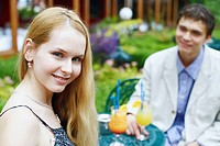 Portrait of a young woman smiling with a young man sitting with her (thumbnail)