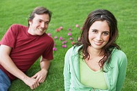 Portrait of a young woman smiling with a mid adult man lying on the grass