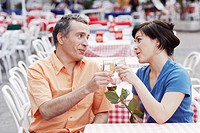 Mature man and a young woman toasting at a sidewalk cafe