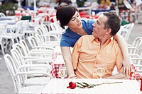 Young woman leaning over a mature man at a sidewalk cafe