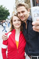 Teenage couple holding a mobile phone for a photograph