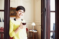Portrait of a mid adult woman holding a glass of red wine and smiling