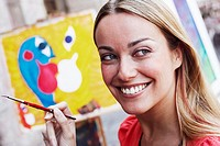 Close-up of a young woman holding a paintbrush and smiling