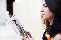 Side profile of a mid adult woman reading a magazine