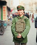 Portrait of a young woman in the army uniform standing in a street