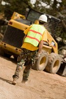 Rear view of a construction worker walking towards a bulldozer